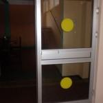 Szklane drzwi z żółtymi kółkami.