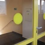 Szklane drzwi z żółtymi kółkami i ramami.