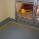żółty pas i szklane drzwi z żółtymi naklejonymi kółkami.
