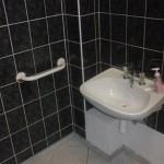 Zdjęcie zlewu w toalecie z widoczną ze specjalnym uchwytem do przytrzymywania się dla osób z niepełnosprawnością ruchową.