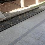 Krawędź peronu i tory kolejowe ze słabo widocznym pasem ostrzegawczym.