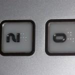 Widok przycisków windzie z oznaczeniami brajlowskimi.