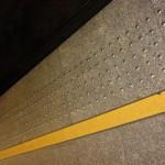 Peron kolejowy z widocznym żółtym pasem i guzkami ostrzegawczymi w pobliżu krawędzi peronu.