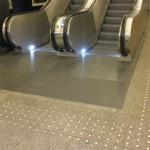 Doskonale oświetlone schody ruchome z guzkami informacyjnymi